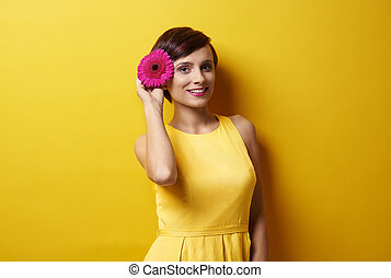 Picture of model holding flower next to ear