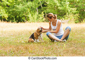 Picture of nice-looking young woman caressing her pure-bred dog otdoors in the summer meadow