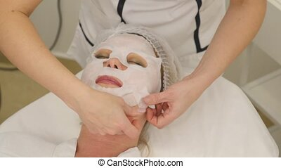 picture of pretty beautician doing rf-lifting procedure for woman laying down in a beauty salon