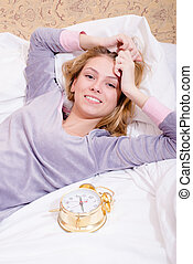 picture of relaxing beautiful blond young woman sexy girl with alarm clock having fun happy smiling & looking at camera on white bed background closeup portrait