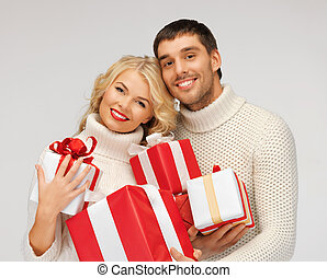 romantic couple in a sweaters with gift boxes - picture of...