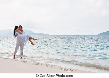 Picture of romantic young couple having a walking on the sea shore