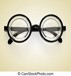 picture of short-sighted glasses on a beige background, with a retro effect
