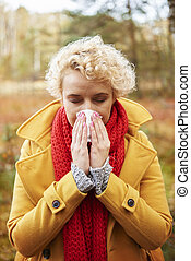 Picture of sneezing woman with tissue in hands