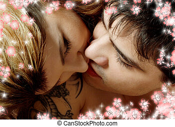 kissing in bed with flowers - picture of sweet couple...