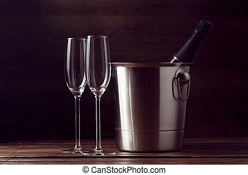 Picture of two empty wine glasses, bottle of champagne