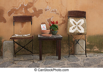 Picture of two small chairs and a little table, in an alley in an old Spanish town
