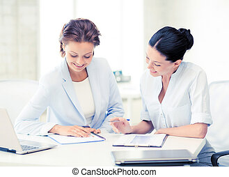 two smiling businesswomen working in office