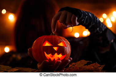 Picture of witch with long hair showing hand on halloween pumpkin
