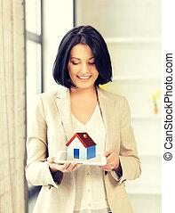 woman holding tablet pc with house illustration