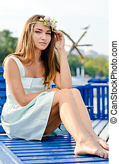 picture of young beautiful stylish blond woman on sea pier relaxing having fun posing in white dress & looking at camera outdoor with copy space background above portrait