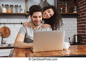 Picture of young couple looking at laptop on table while having breakfast in kitchen at home
