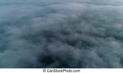 Picturesque 4k aerial drone shot of camera flying through dense fog heavy rain cloud in grey sky over mountain forest