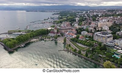 View from drone of lake Leman and houses of swiss city Lausanne in cloudy summer day