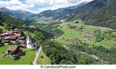 Picturesque aerial view of houses of small Swiss village Cavardiras in mountain valley in sunny summer day. High quality 4k footage