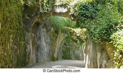 Picturesque alley with stone arches in park of Quinta da Regaleira, Sintra, Portugal
