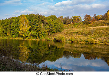 Picturesque autumn landscape with a view of the lake and forest in the background