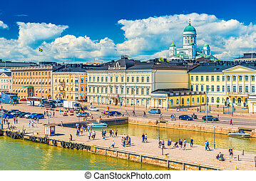 Picturesque cityscape of Helsinki, Finland. View of the city center with historical buildings, The Cathedral, beautiful clouds in the blue sky and people walking along an embankment