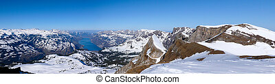 picturesque deep winter mountain landscape in the Alps of Switzerland with a turquoise lake below