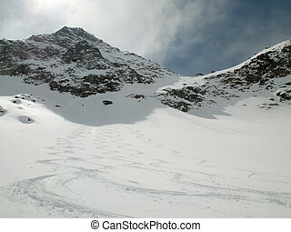 picturesque deep winter mountain landscape in the Alps of Switzerland with backcountry ski tracks in fresh powder