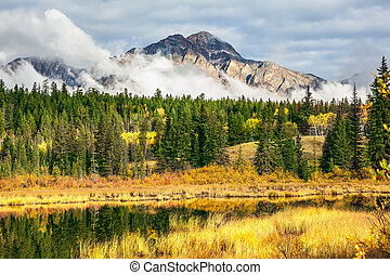 Patricia Lake. Picturesque little lake surrounded by yellow and orange autumn grass and trees. Jasper National Park in the Rocky Mountains