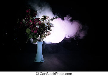 Picturesque purple spring flowers in glass vase standing in a row on a dark background with stars with light and fog. Close up