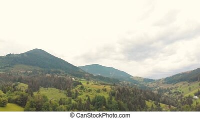 Picturesque spring Carpathians landscape. Aerial view of mountains slopes, forests on cloudy sky background. Peacefulness.