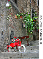 Nice picturesque street in Tuscany with small red bicycle at the front