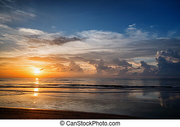 Picturesque sunset over a calm ocean. Phuket, Thailand