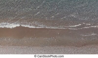 picturesque transparent sea waves roll on brown sandy beach...
