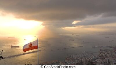 Picturesque view from the Rock of Gibraltar to waving flag of Gibraltar the sea