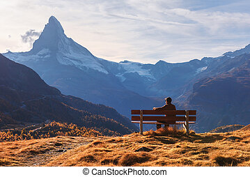 Picturesque view of Matterhorn peak and tourist sitting on wooden bench