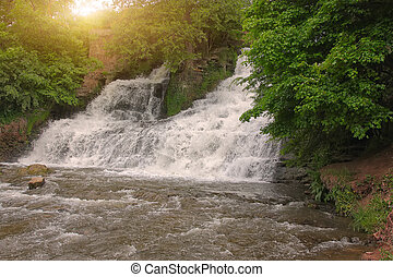 picturesque waterfall in the forest at sunset