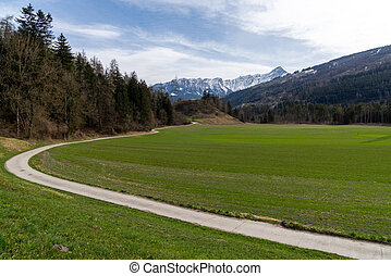 mountain landscape in the Swiss Alps with snow-covered peaks and green meadows in the spring