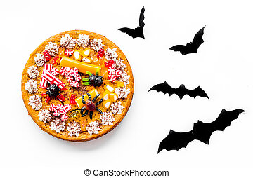 Pie for halloween with gummy spiders near paper bats on...