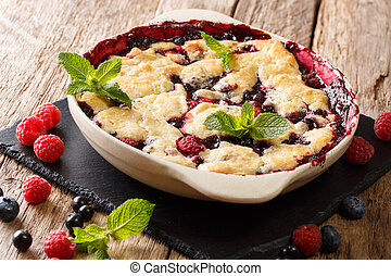 Pie sweet cobbler of raspberries, currants and blueberries close-up in a dish for baking. horizontal
