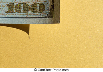 Piece of 100 dollar bill at the upper-left corner on the golden yellow background. Conceptual photo, minimalistic design