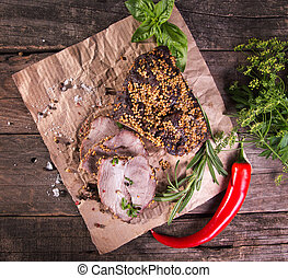 Piece of baked cold-boiled pork meat in mustard grains served with rosemary, basil and chili pepper.
