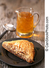 Baklava, delicious pastry dessert made with phyllo dough, nuts, butter and sugar served on a plate with a jar of honey