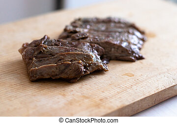 Piece of beef steak on a wooden board in a closeup view