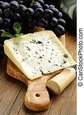piece of blue cheese with grapes