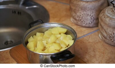 Piece of Butter Falls into the Potatoes in a Saucepan on the Home Kitchen. Slow Motion