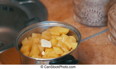 Piece of Butter Falls into the Potatoes in a Saucepan on the Home Kitchen