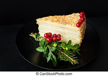 piece of cake decorated Christmas tree and red berries on a black background