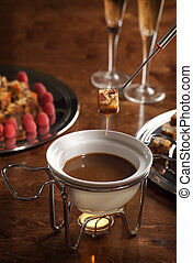 chocolate fondue - piece of cake dipped into a chocolate...