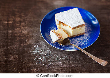 Piece of cake on a plate on wooden table background.