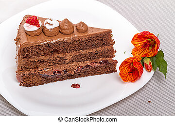 Piece of cake on a white plate and flower