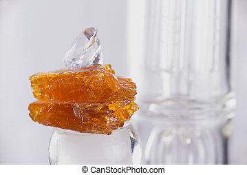 Piece of cannabis oil concentrate aka shatter over a glass rig isolated