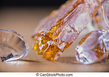 Piece of cannabis oil concentrate aka shatter with glass rig and diamonds