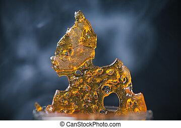 Piece of cannabis oil concentrate aka shatter with smoke -...